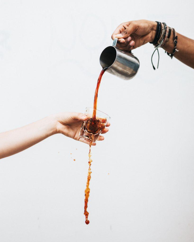 Pessoa servindo café para outra pessoa em um copo de vidro quebrado.