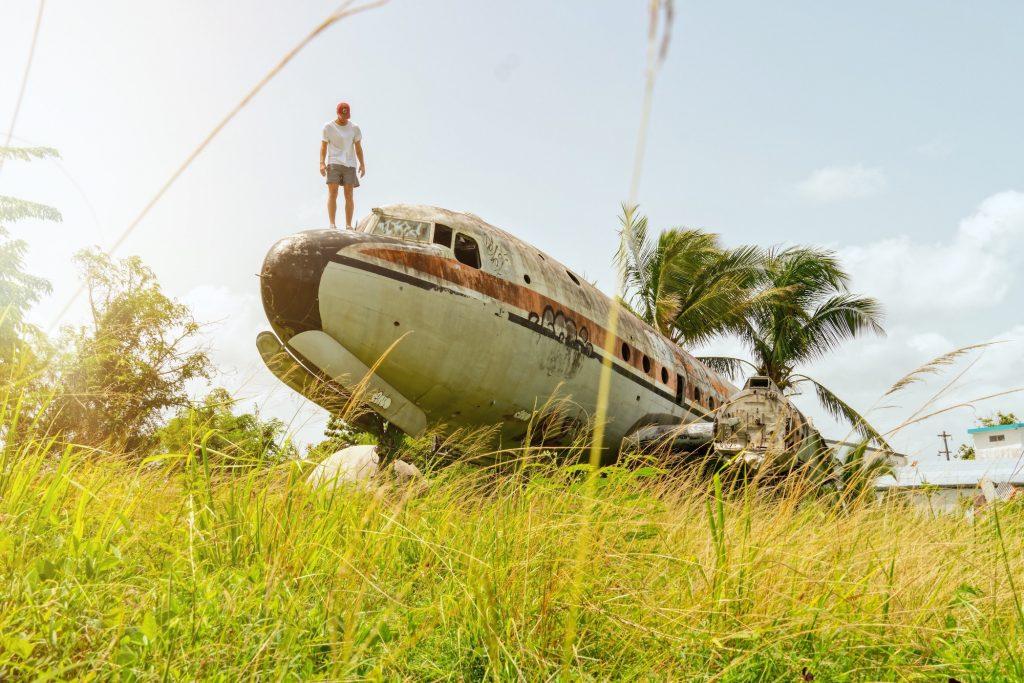 Pessoa em cima de um avião abandonado.