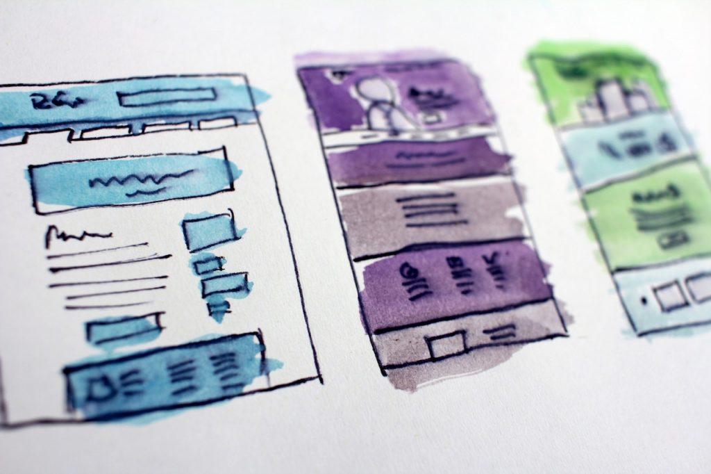 Desenho em papel com 3 rascunhos de telas de aplicativos.