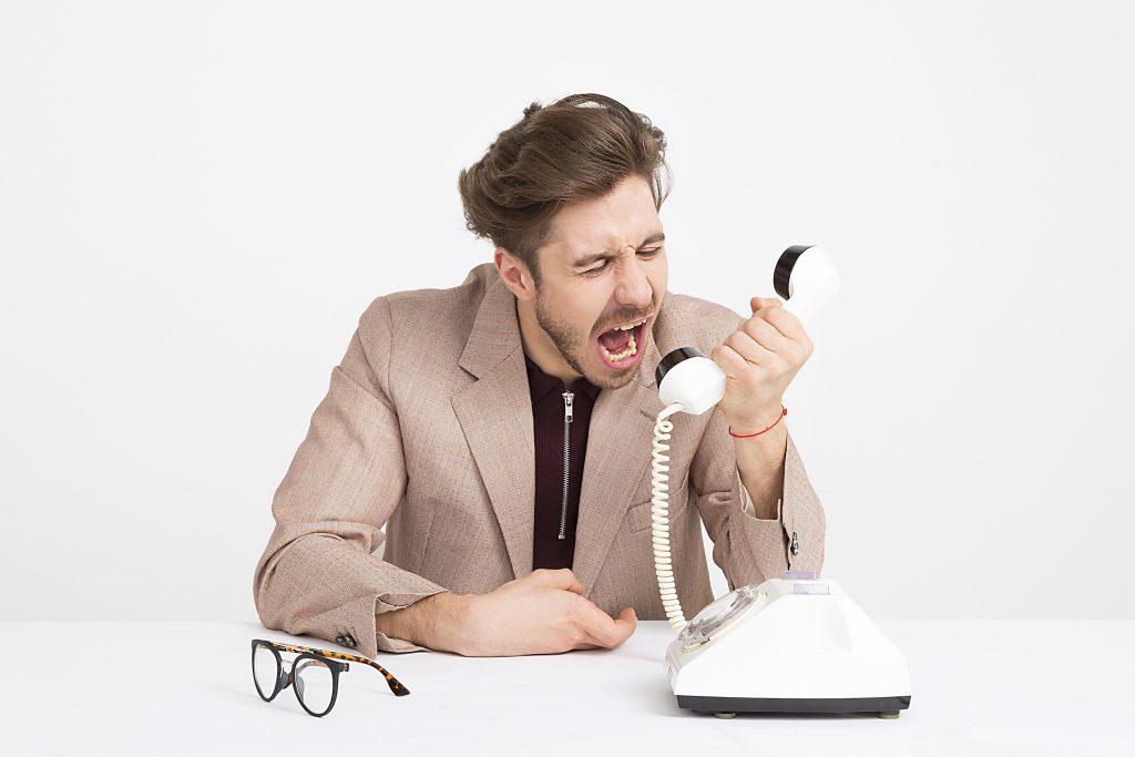 homem gritando com telefone analógico