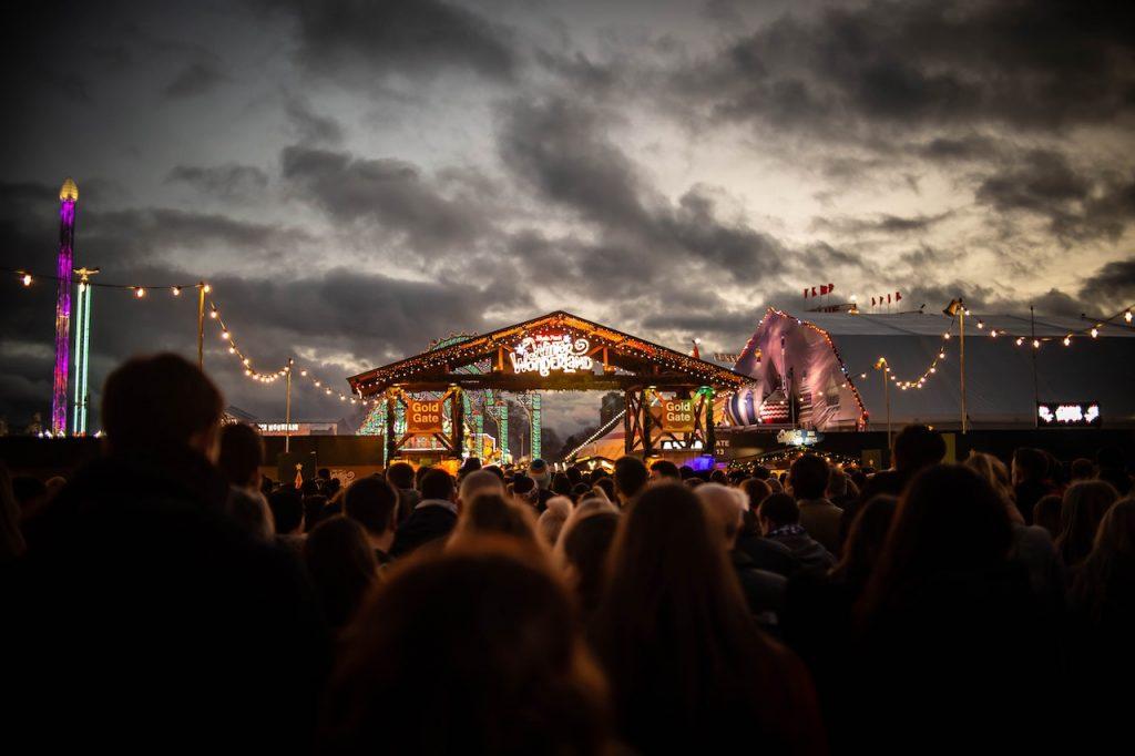 Centenas de pessoas de frente para um palco simples de madeira em um festival.