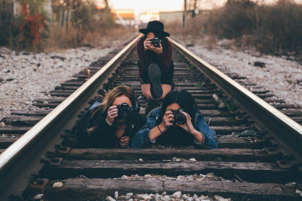 três garotas com câmeras fotográficas no trilho do trem tirando fotos