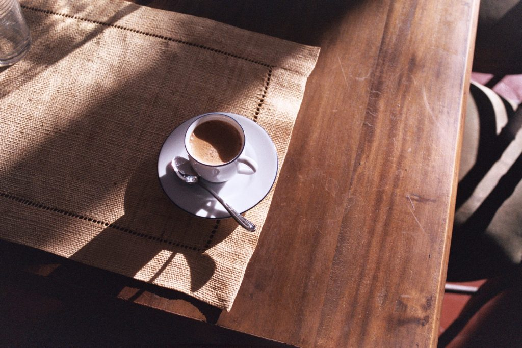 Xícara de café com uma colher no pires